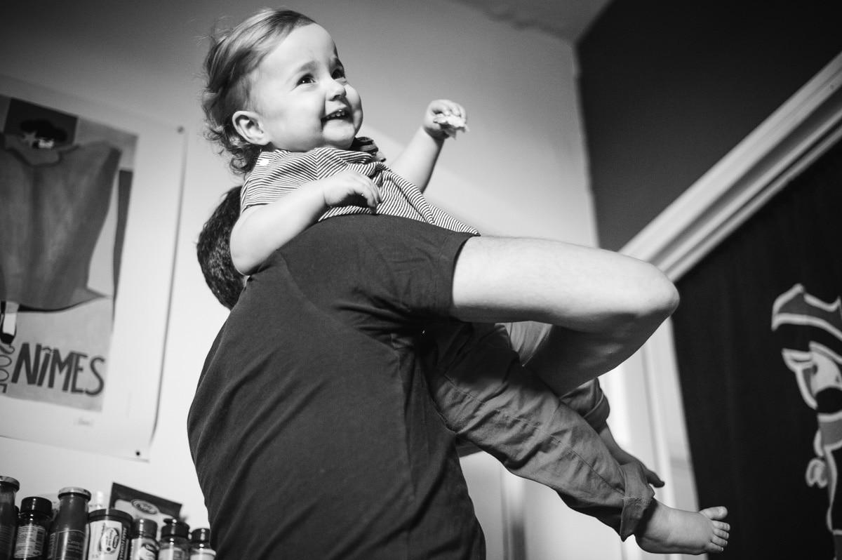 une petite fille grignotte un gâteau dans les bras de son papa dans leur cuisine à Paris