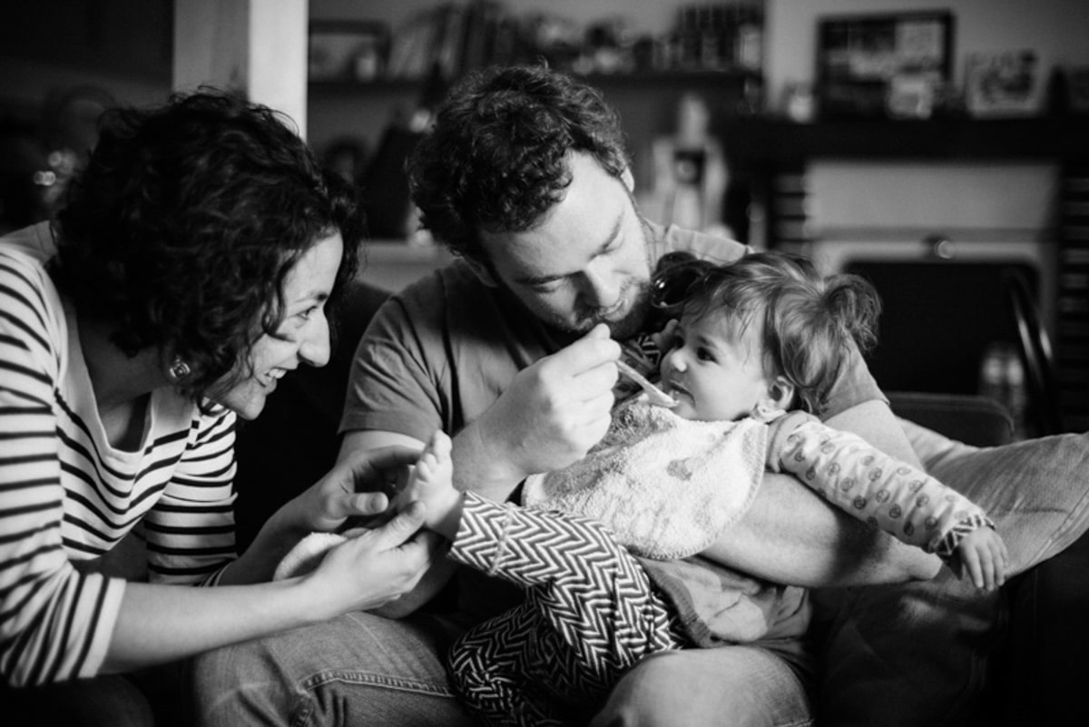 une petite fille mange sur les genoux de son papa pendant que sa maman lui chatouille les pieds