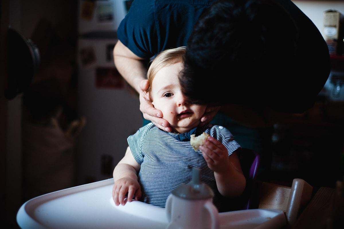 Un papa embrasse tendrement le front de sa petite fille qui prend son goûter dans leur cuisine à Paris 19.
