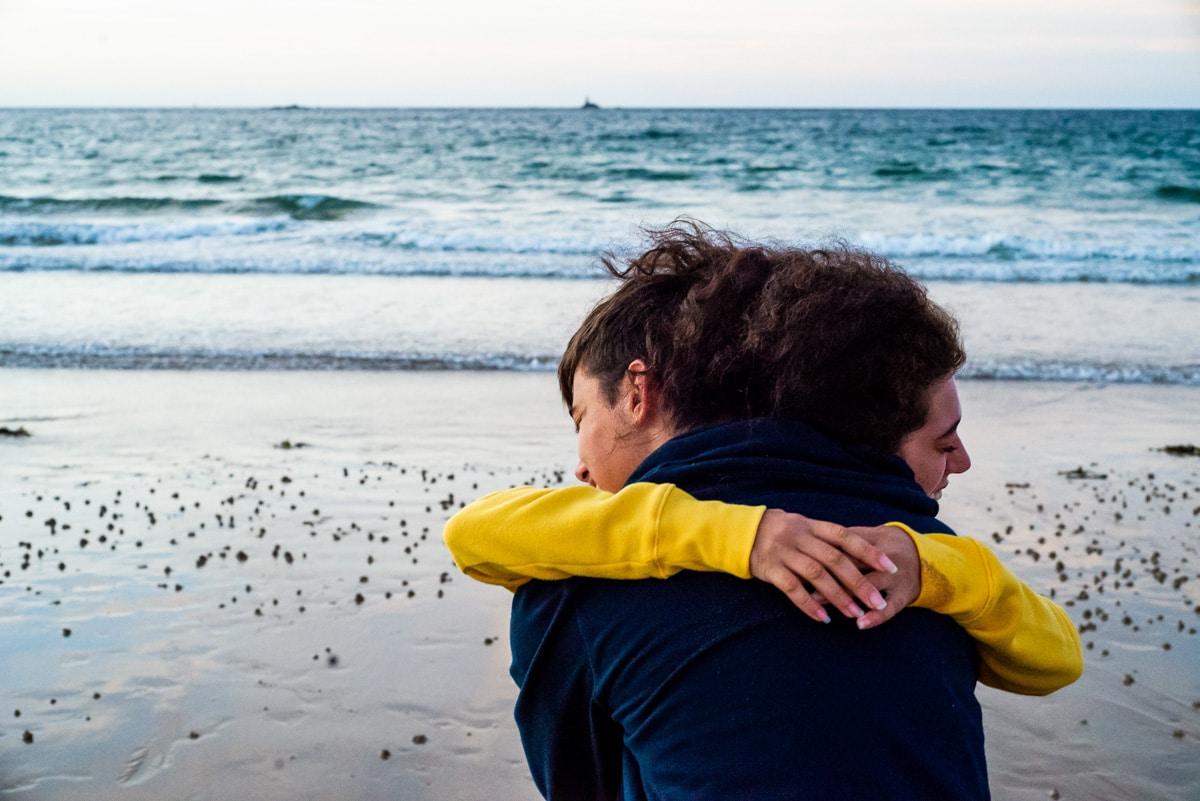 un frère et une soeur d'étreignent sur la plage de Saint Briac sur Mer pendant les vacances