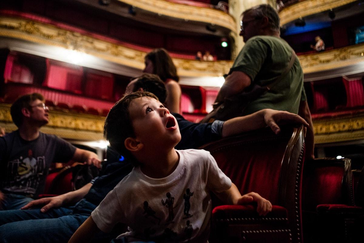 Un enfant regarde ébahit les décors de l'opéra de Lille pendant une visite en famille.