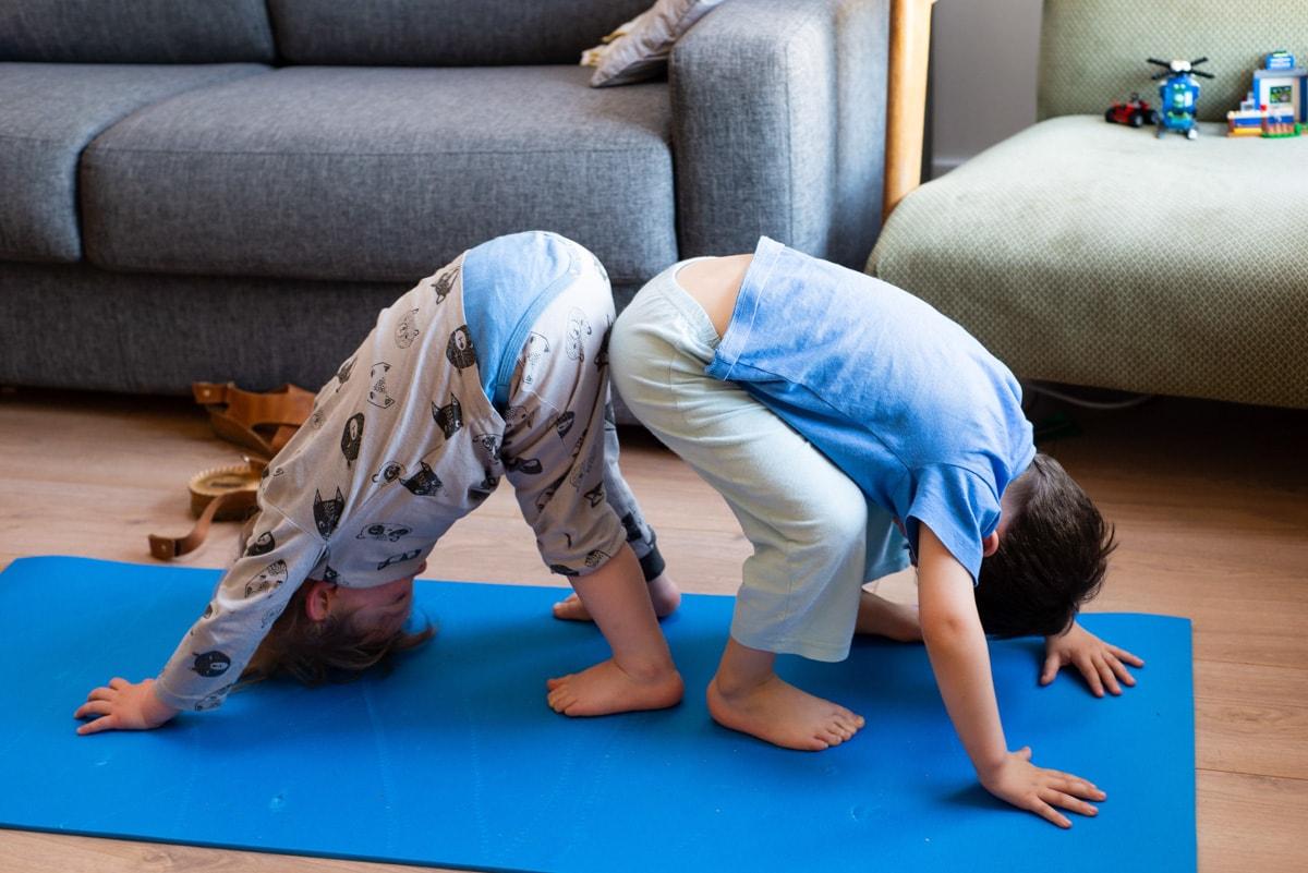 deux garçons font le chien tête en bas sur un tapis de yoga dans un appartement à Nantes