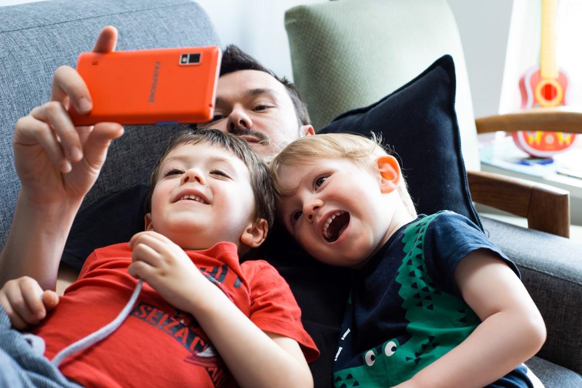 deux enfants et leur papa regardent des photos sur un téléphone dans un canapé à Rezé