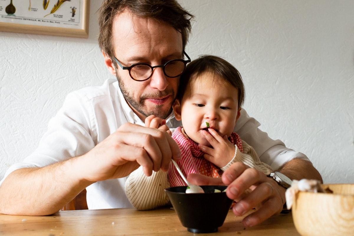 un bébé japonais mange sur les genoux de son papa français à leur domicile au Mans