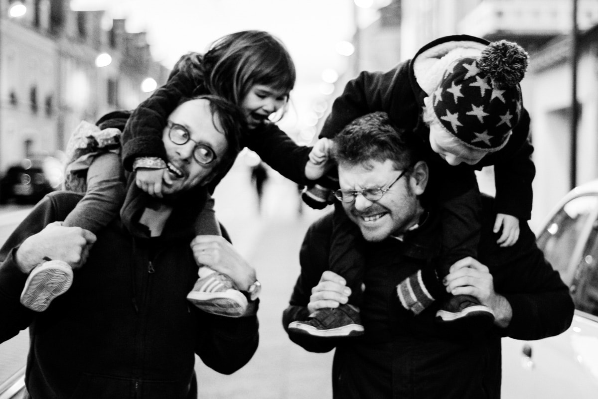 deux papa portent leurs enfants qui se chamaillent sur leurs épaules dans les rues d'Angers