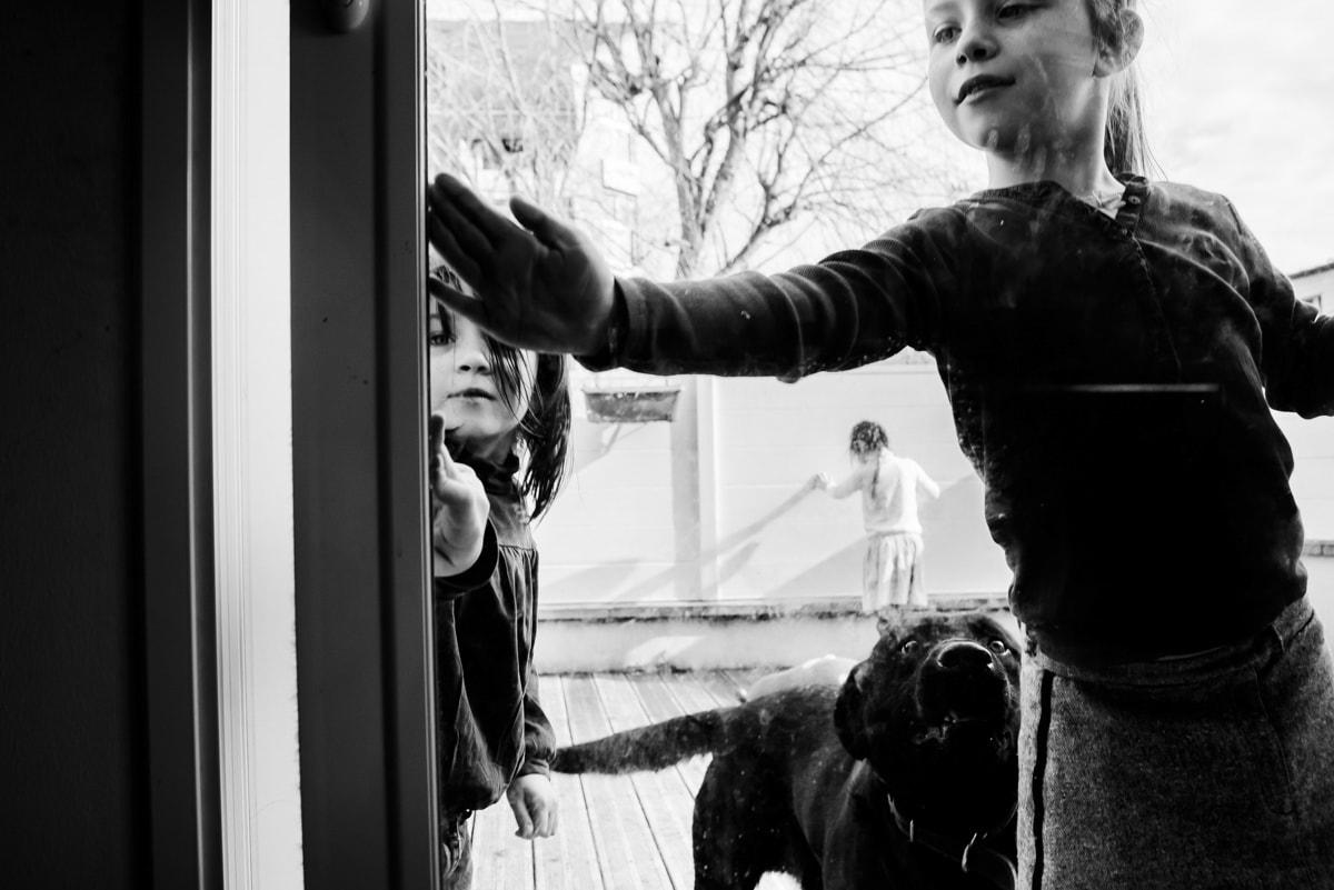 Deux fillettes ferment la porte vitrée de leur terrasse à Nantes.