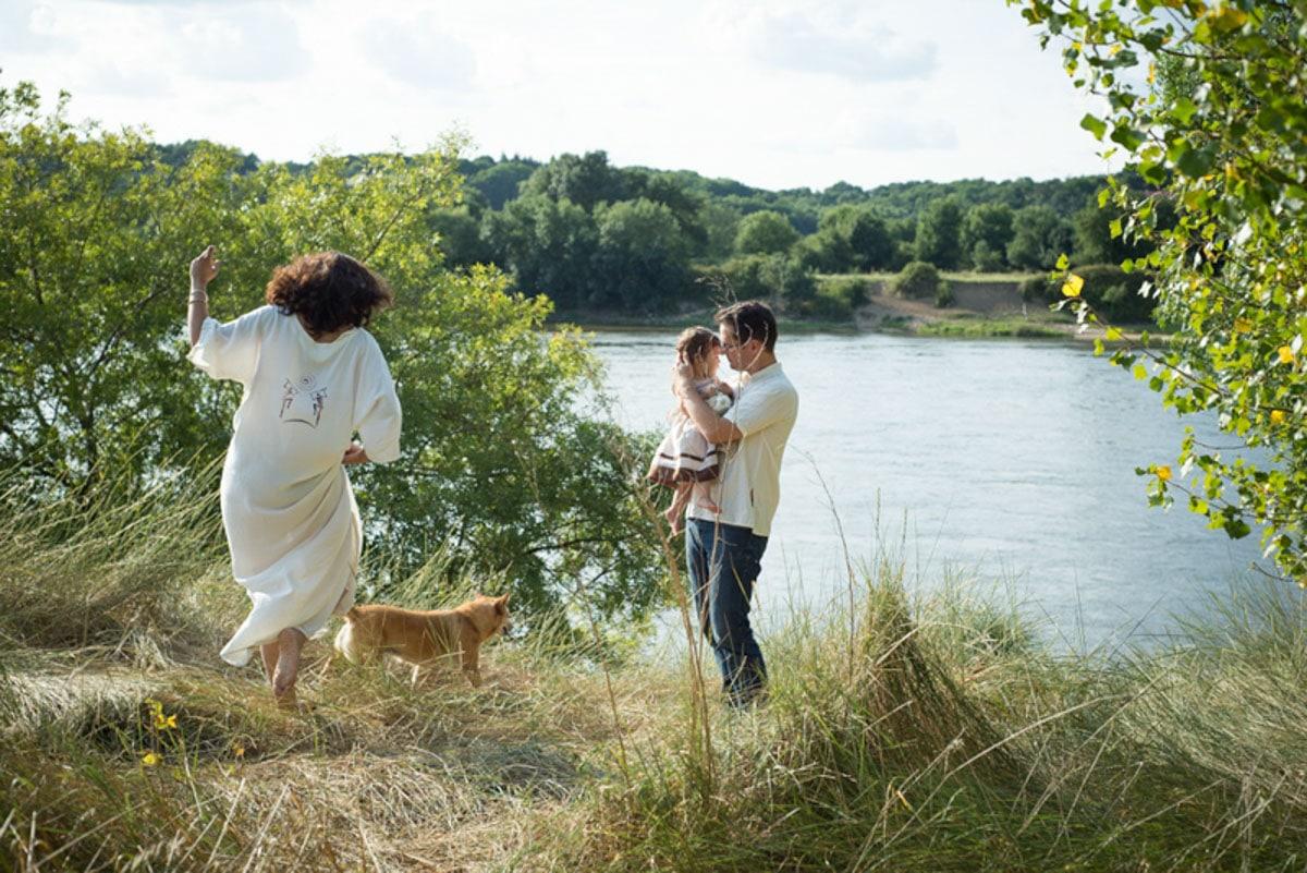 une femme enceinte marche dans les hautes herbes en bord de Loire et son mari tient leur fillette à Champtoceaux