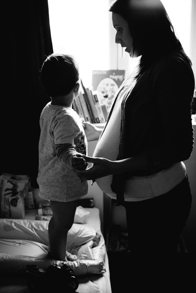 Une femme enceinte parle a son fils debout sur la table à langer à Cholet