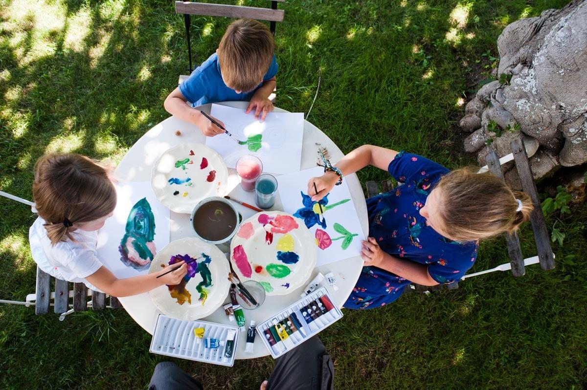 trois enfants font de la peinture sur la table du jardin à l'ombre d'un figuier à Noirmoutier