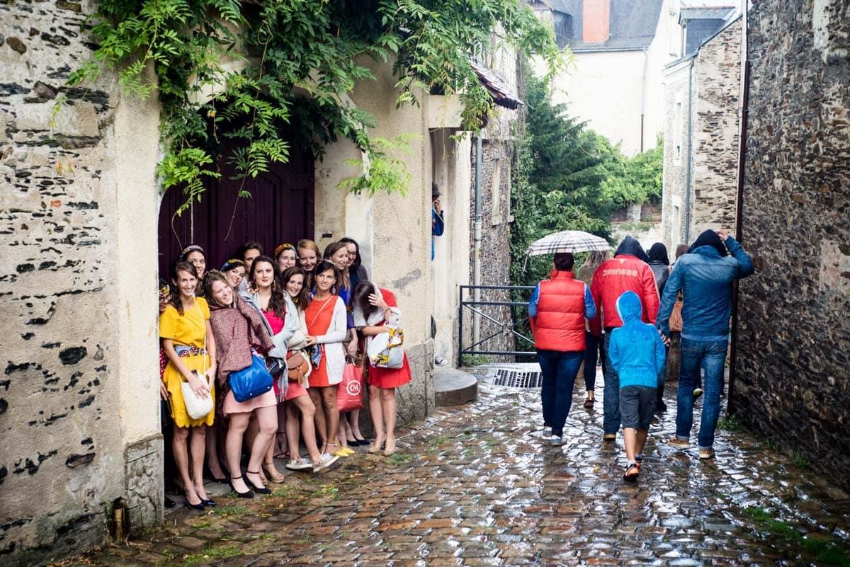 une groupe de fille se protègent de l'averse sous un porche dans les rues de la Cathédrale à Angers.