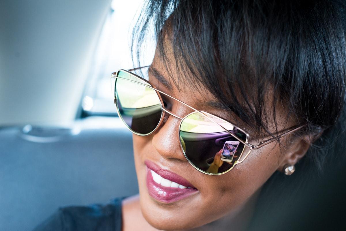 à l'arrière d'une voiture, la mariée regarde par la fenêtre, elle porte de grande lunettes miroitantes.