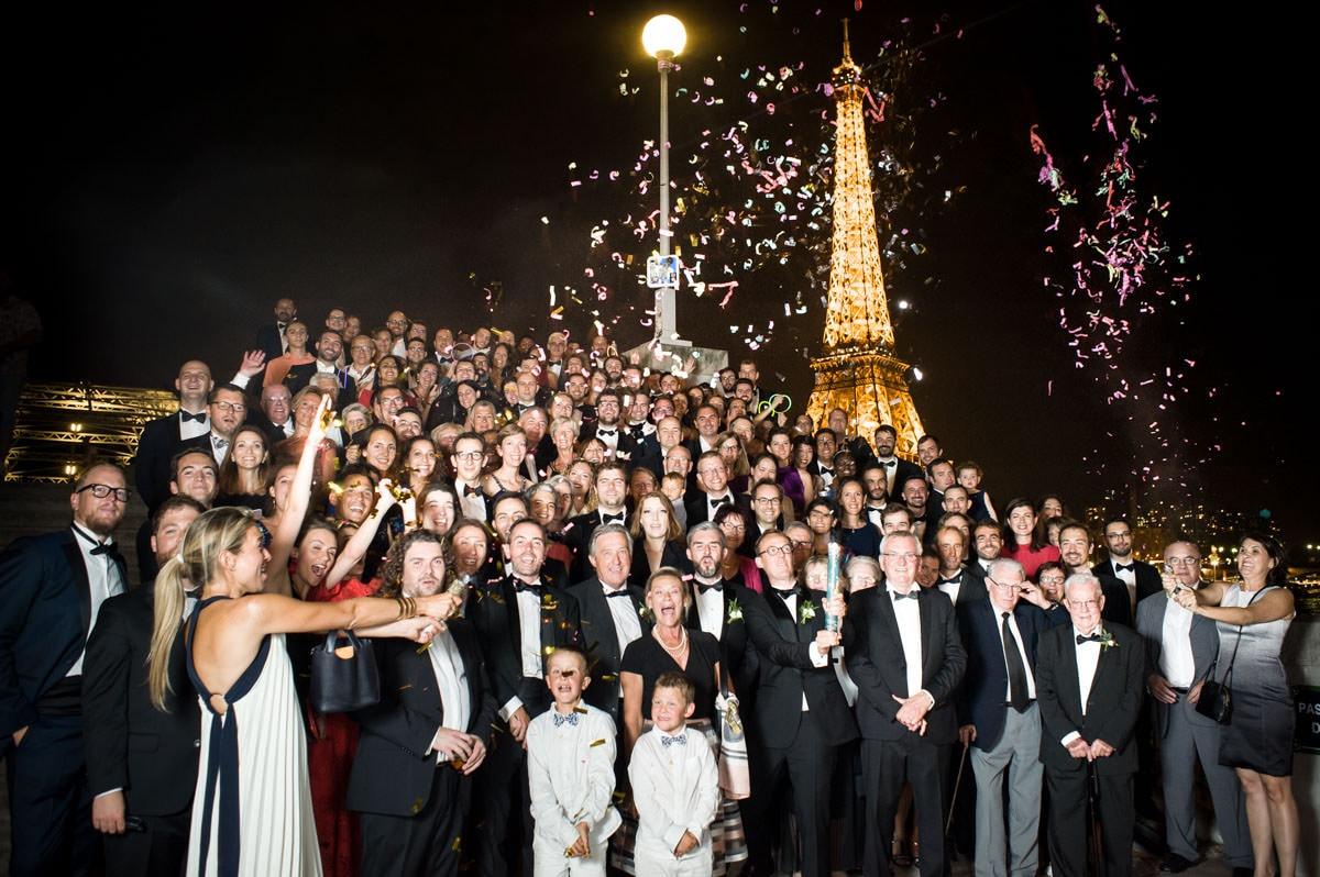 Photo de groupe sur la passerelle Debilly, de nuit, devant la tour Eiffel qui scintille