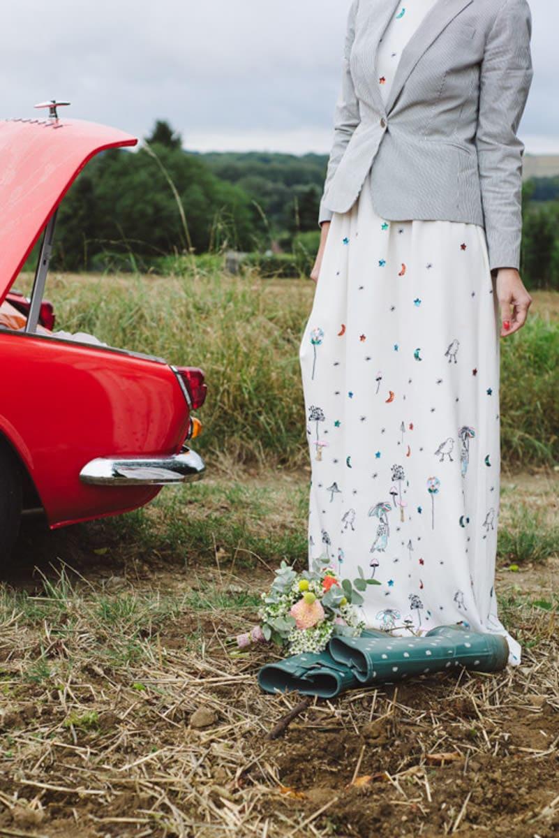 La mariée en robe Manoush se tient debout à l'arrière de laa Spitfire rouge avec ses bottes en caoutchouc et son bouquet d'eucalyptus