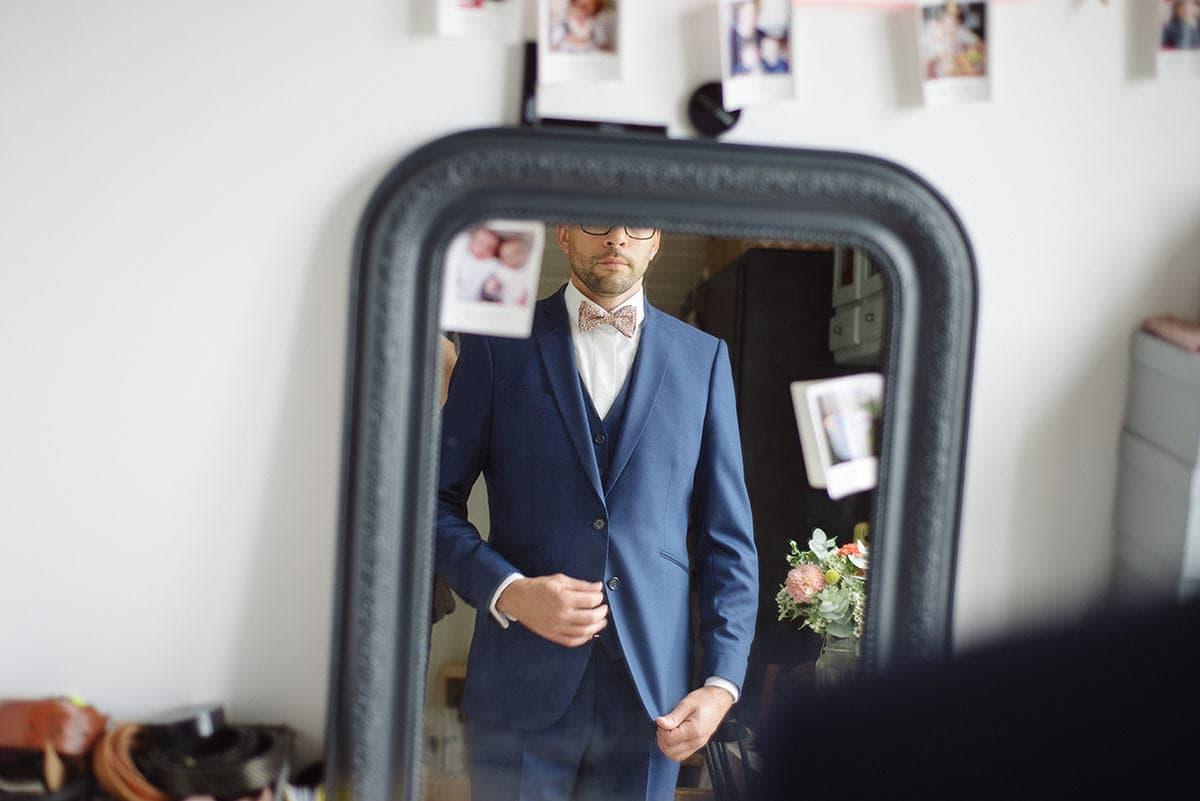 Le marié ajuste son costume devant le miroir de sa chambre à Paris