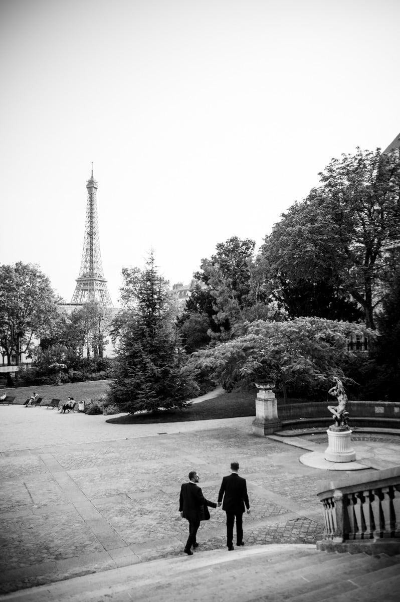 Un couple d'hommes se tient par la main dans les jardins du musée Galiera devant la tour Eiffel