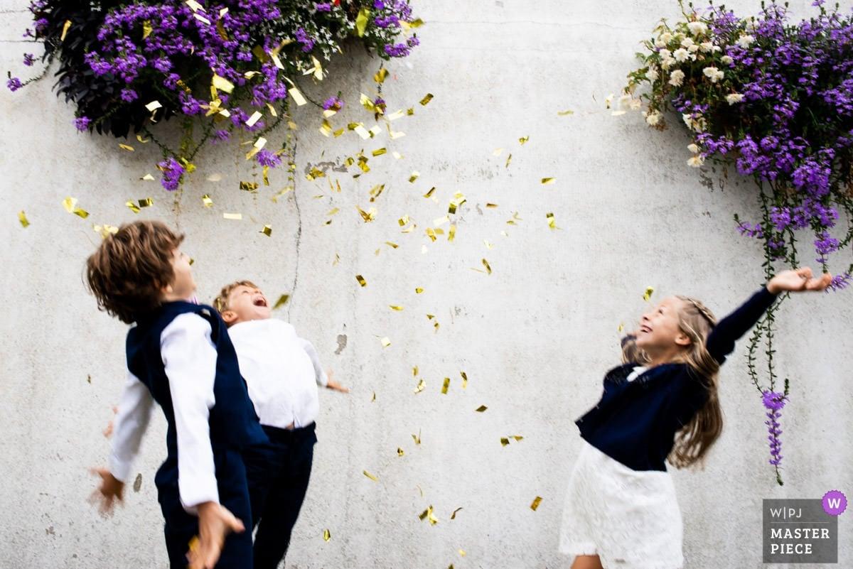 Des enfants jettent des confettis dorés en l'air à la sortie de la mairie de Pornic