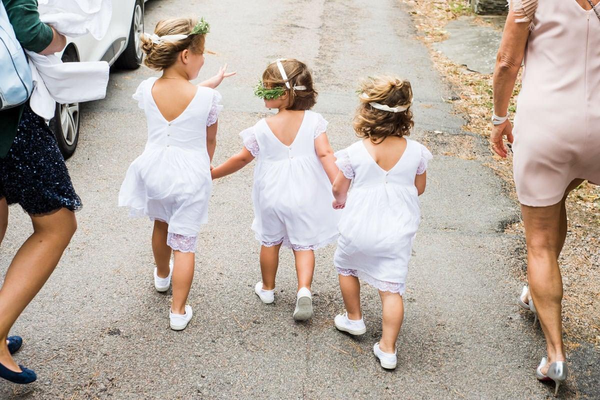 Trois petites demoiselles d'honneurs en robe blanches marchent dans le vent pour rejoindre l'Eglise de Saint Marie de la Pornic