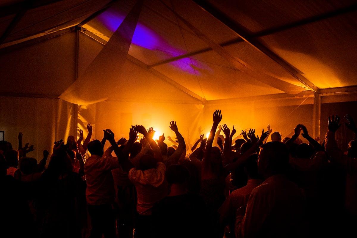 Tous les invités dansent et lèvent les bras en l'air pendant un mariage sous une tente blanche éclairée de jaune