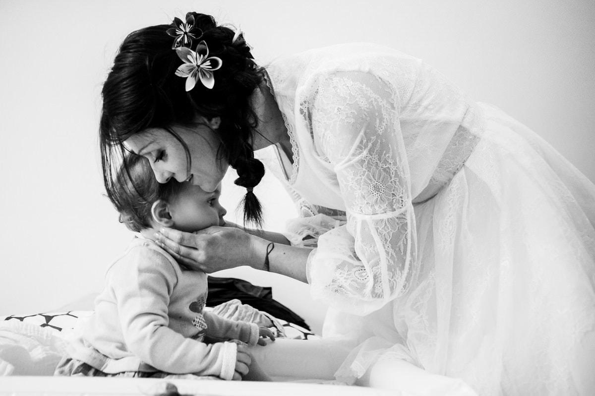 La mariée embrasse tendrement sa petite fille pendant les préparatifs de son mariage à Sarzeau