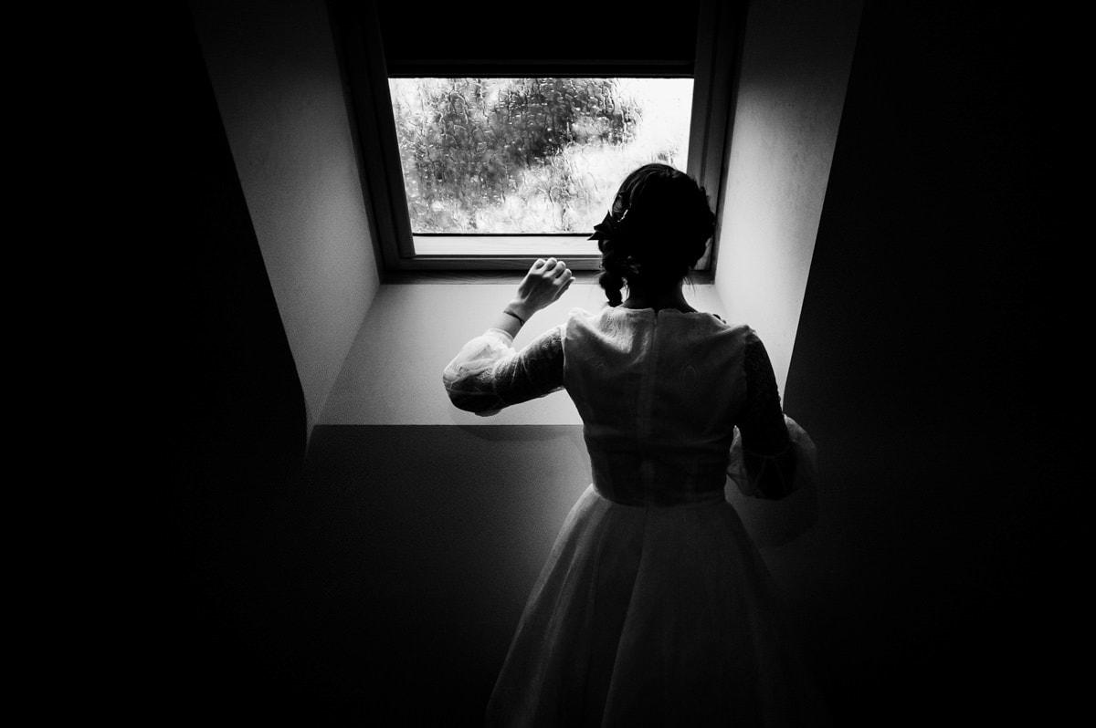 La mariée regarde la pluie tomber sur le Velux en attendant son mariage à Sarzeau