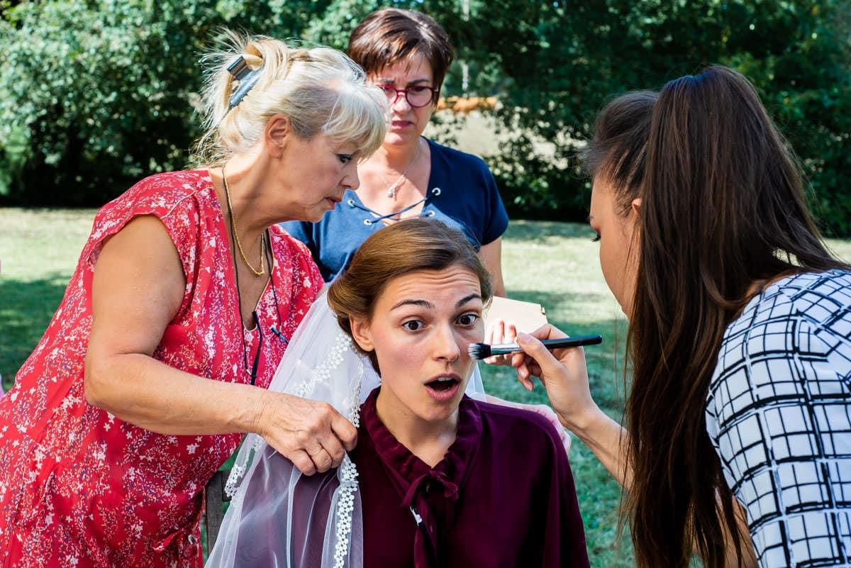 coifeuse, maquilleuse, maman s'affairent autour de la mariée qui se prépare dans son jardin à Bouchemaine
