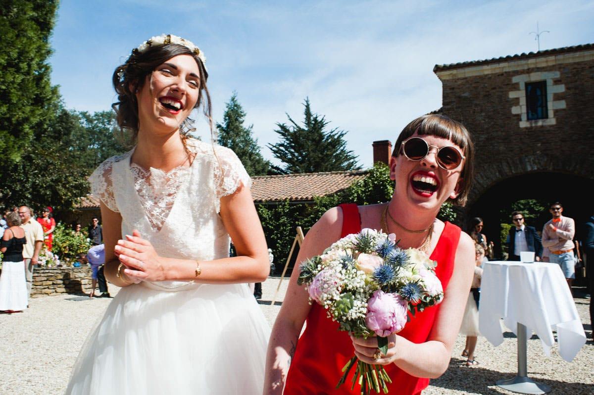 La mariée et sa copine en robe rouge qui vient d'attraper le bouquet, éclatent de rire dans la cour du château de la Colaissiere.