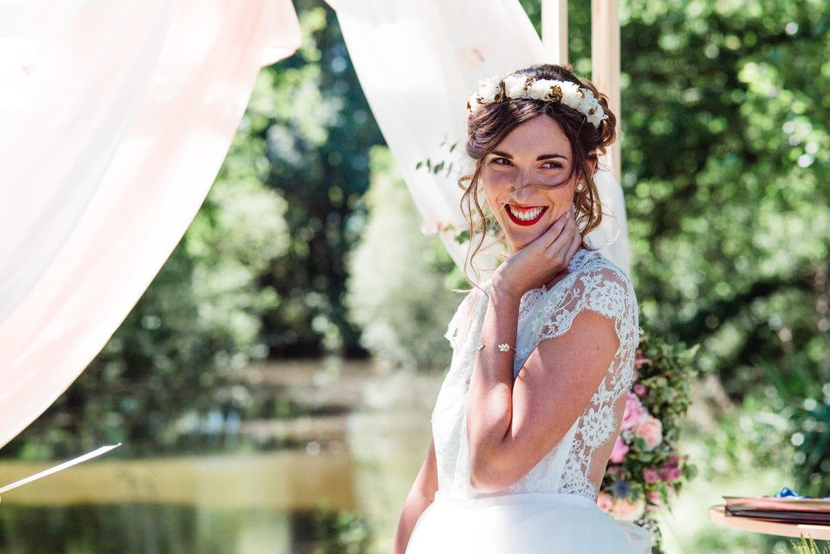 La mariée a un large sourire pendant la cérémonie laïque de son mariage au château de la colaissière