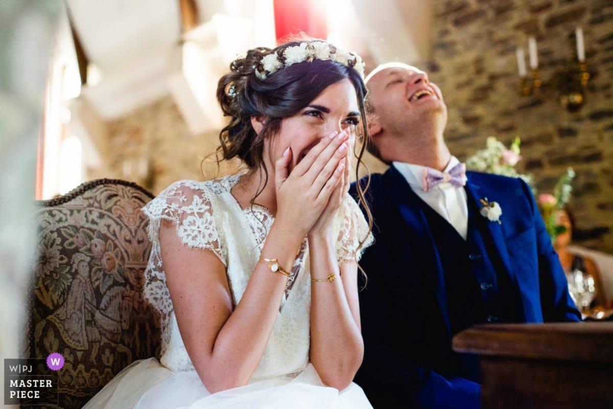Les mariés rigolent devant la vidéo des boulettes de papier au château