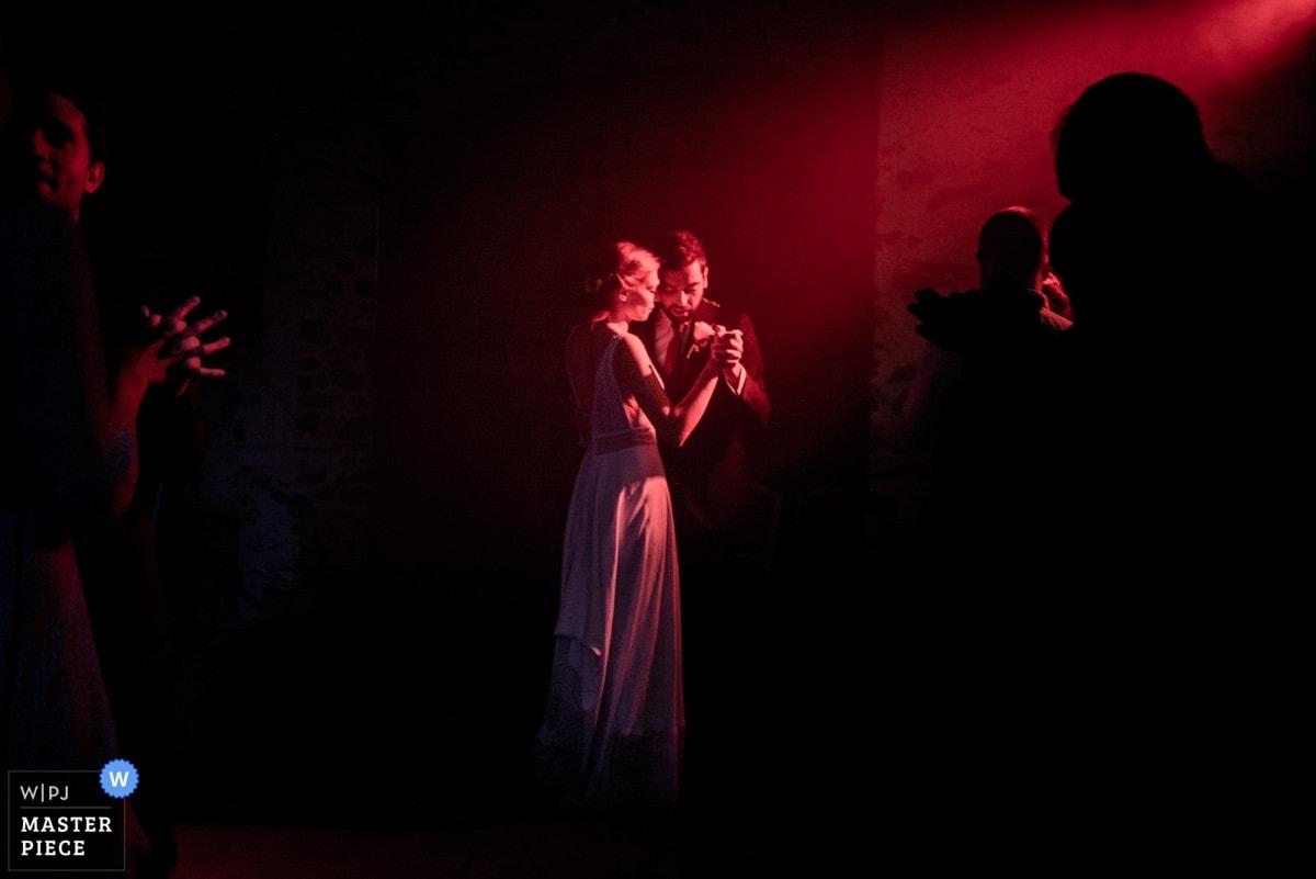Les jeunes mariés ouvrent le bal dans une lumière tamisée rouge au château de la Fresnay à Saint Aubin sur Ligné