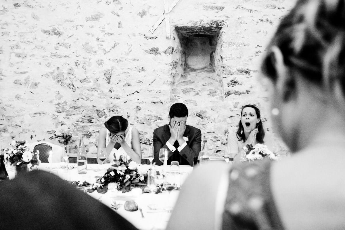 Les mariés se cachent le visage dans leurs mains pendant le discours hilarant de la témoin