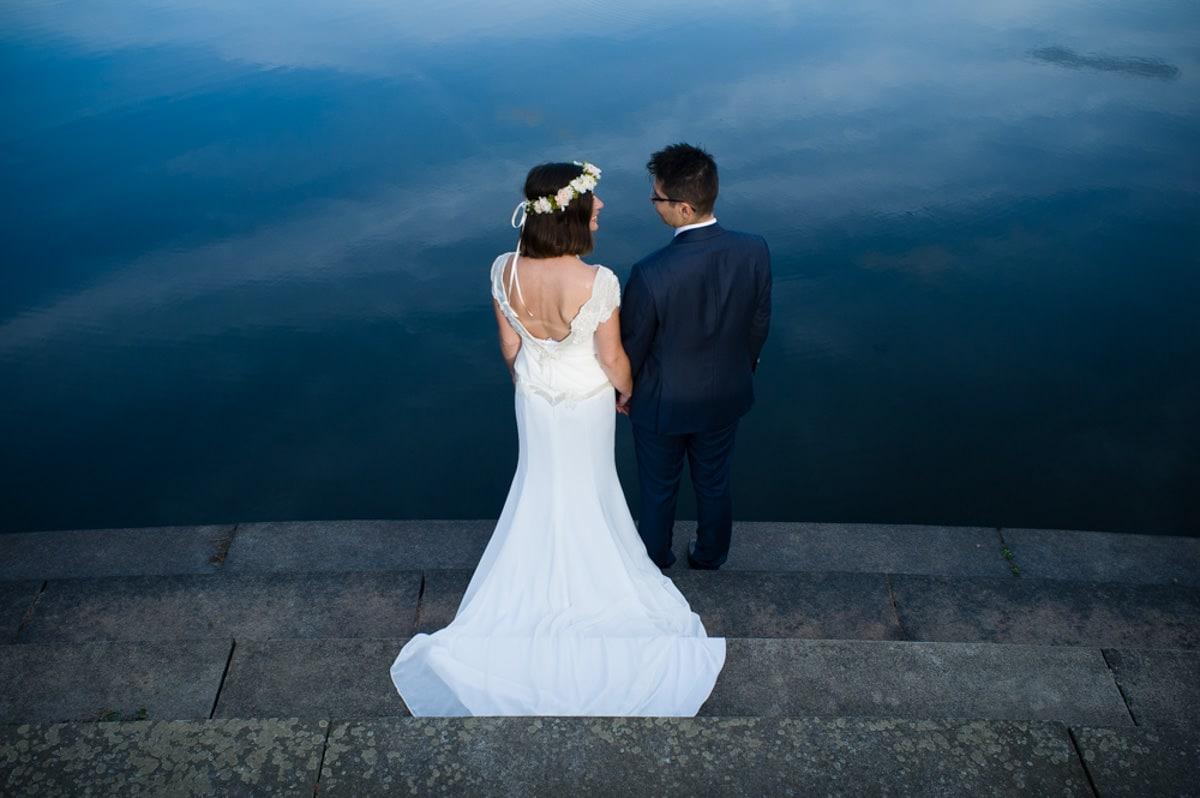 Les mariés devant le lac du château de Serrant partagent un regard complice