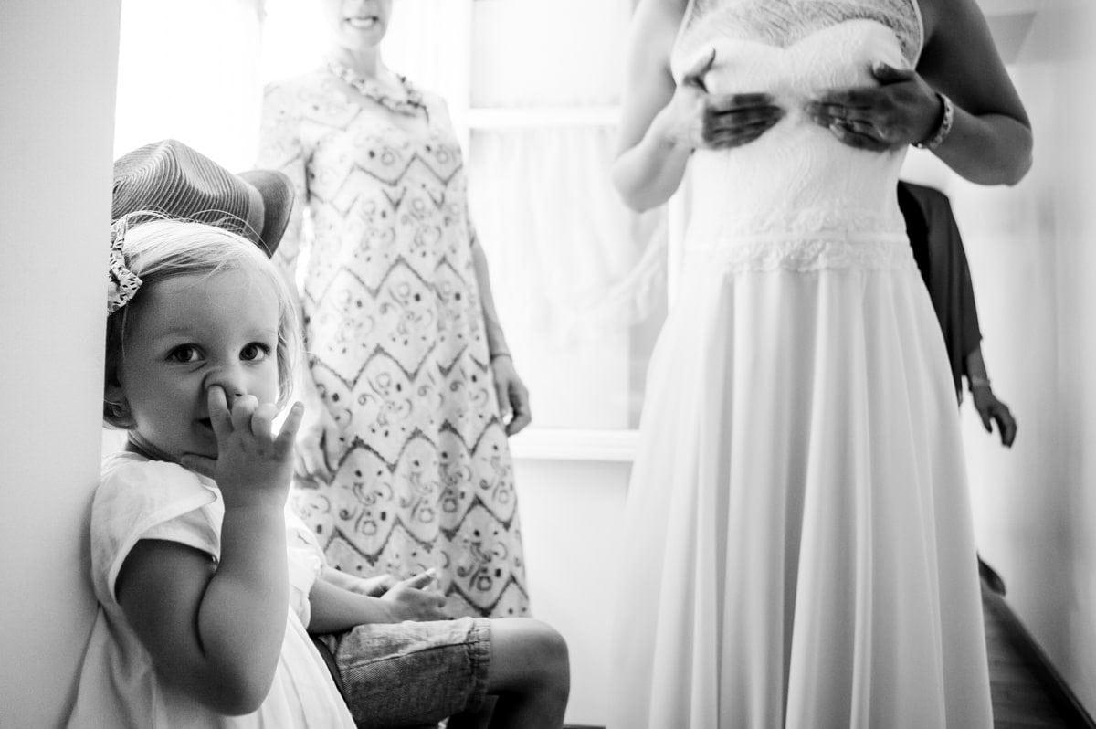 la fille de la mariée les doigts dans le nez pendant que sa maman ajuste sa robe au Jardin Cleray