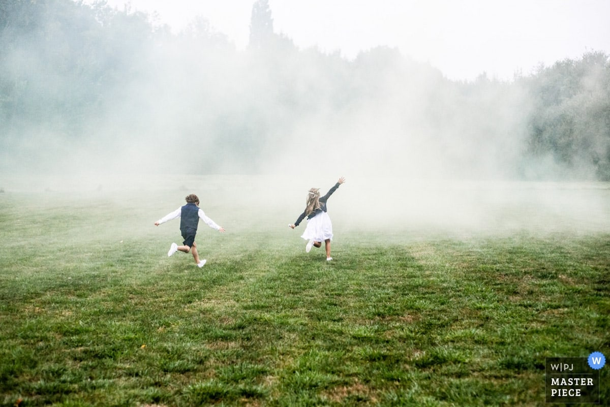 Deux enfants courent dans les fumigènes au parc du Manoir de la Jahotière