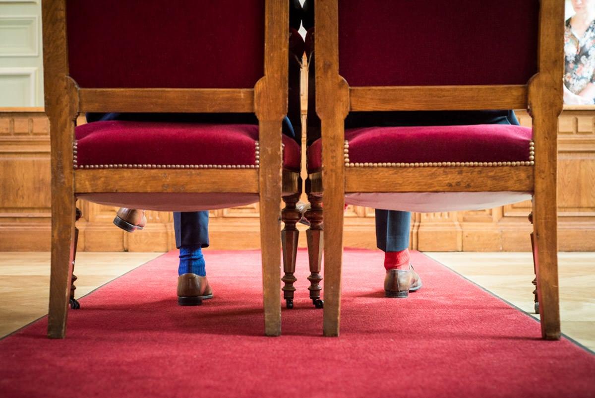 deux hommes se marient, ils sont assis sur les chaises de la mairie du 3eme à paris, on ne voit que leurs chaussettes bleu et rouge.