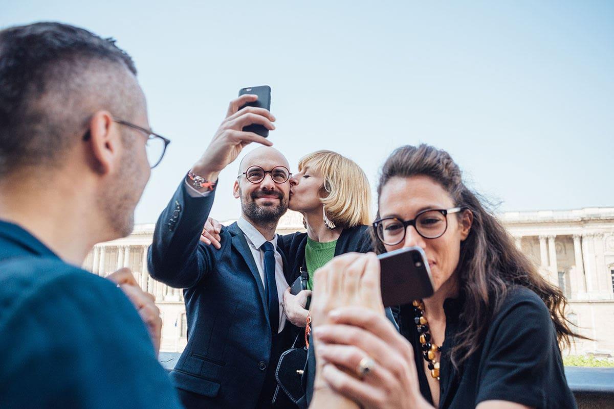 Les invités font des selphies devant le Louvre du haut de la terrasse de la mairie du 1er à Paris