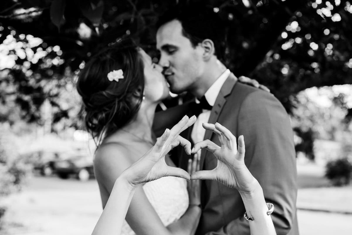 Les mariés s'embrassent et au premier plan, deux mains forment un coeur.
