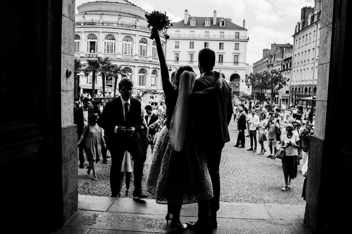 La mariée lève son bouquet triomphalement à la sortie de la mairie de Rennes