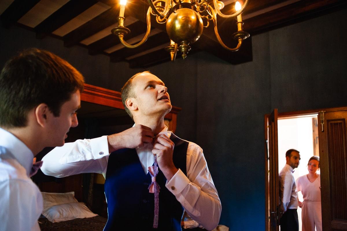 Le marié ferme le dernier bouton de sa chemise
