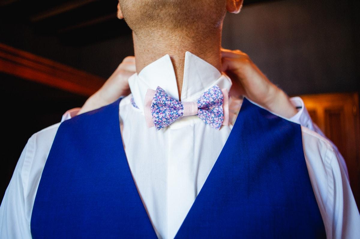 Le frère du marié l'aide à ajuster son noeud papillon de la marque Le Lucien en tissus Liberty