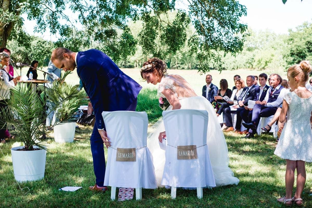 Les mariés s'installent sur leurs chaises avec des écriteaux Le Marié et La Mariée.