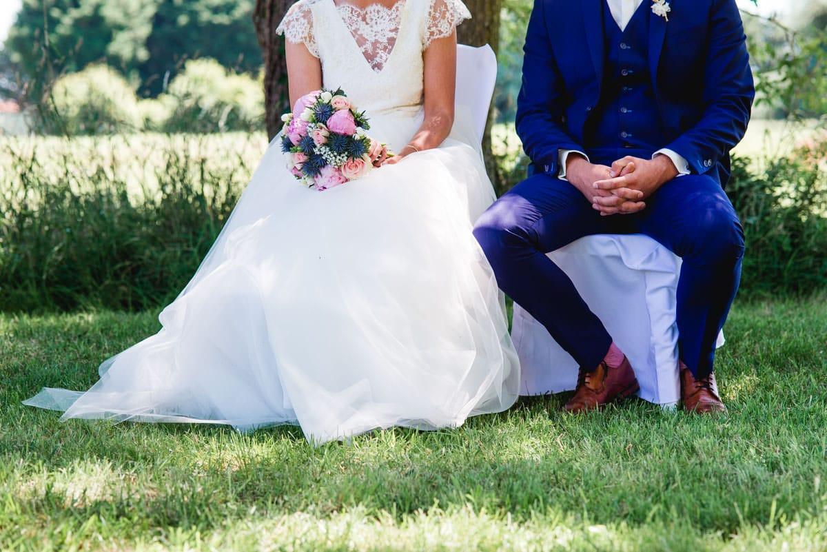 Les mariés sont assis sur leur chaise pendant la cérémonie laïque au château de la Colaissière
