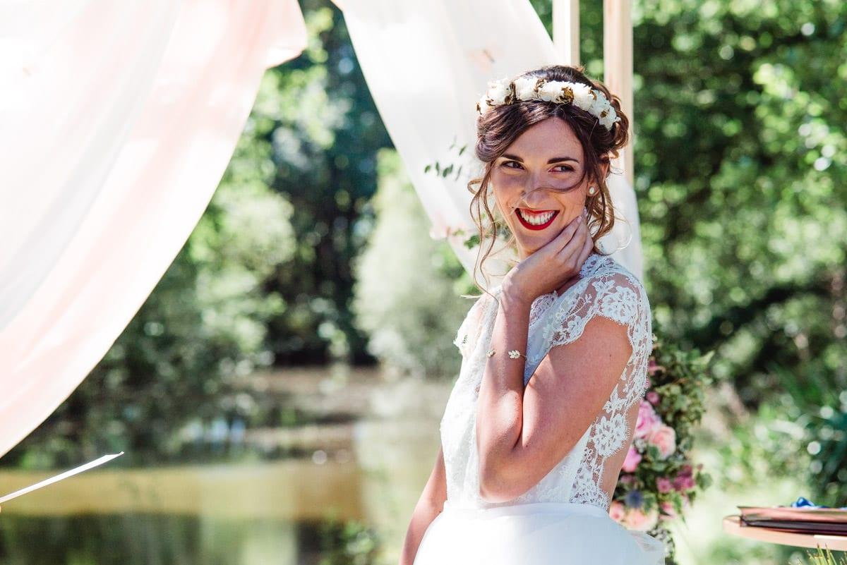 La mariée sourit à l'écoute du discours, ses cheuveux volent au vent.