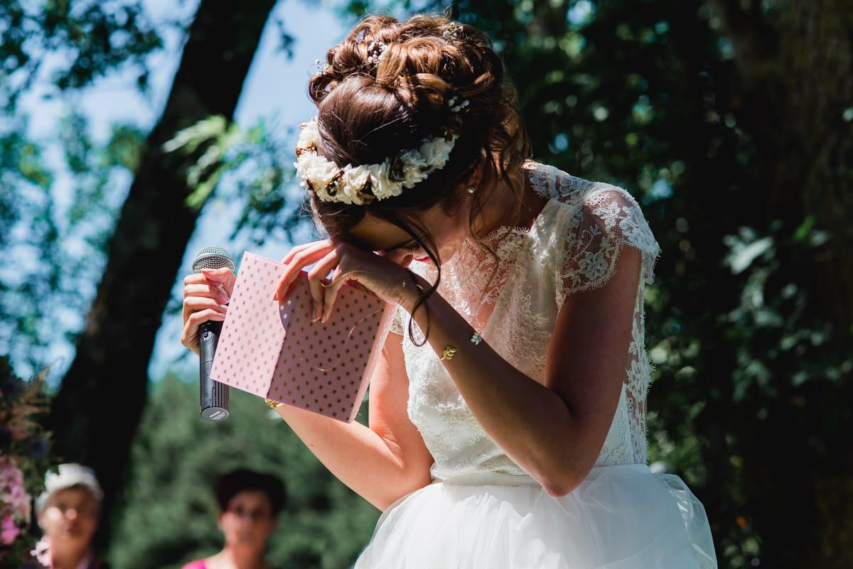 La mariée rie et se cache le visage pendant la lecture de ses voeux lors de la cérémonie laïque de son mariage au château de la Colaissière