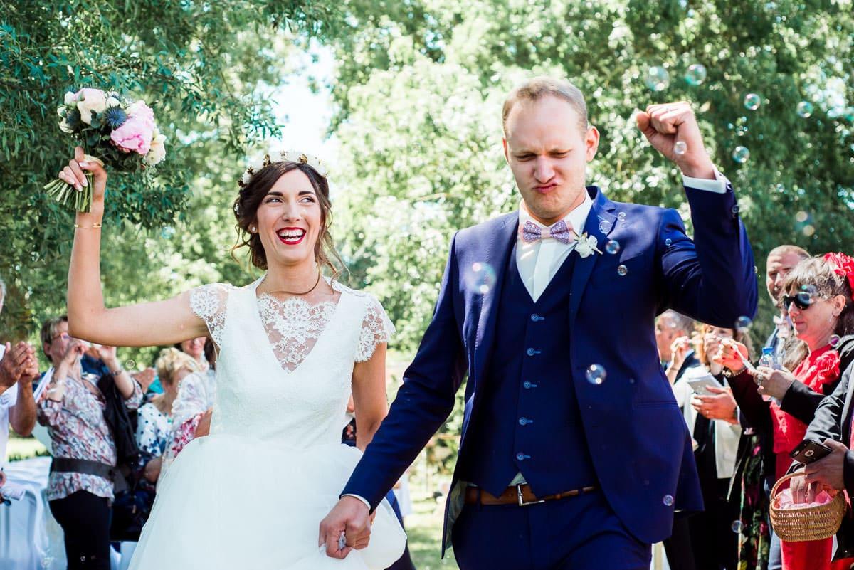 Les mariés sont heureux en marchant parmis meurs invités après la cérémonie laïque de leur mariage au château de la colaissiere