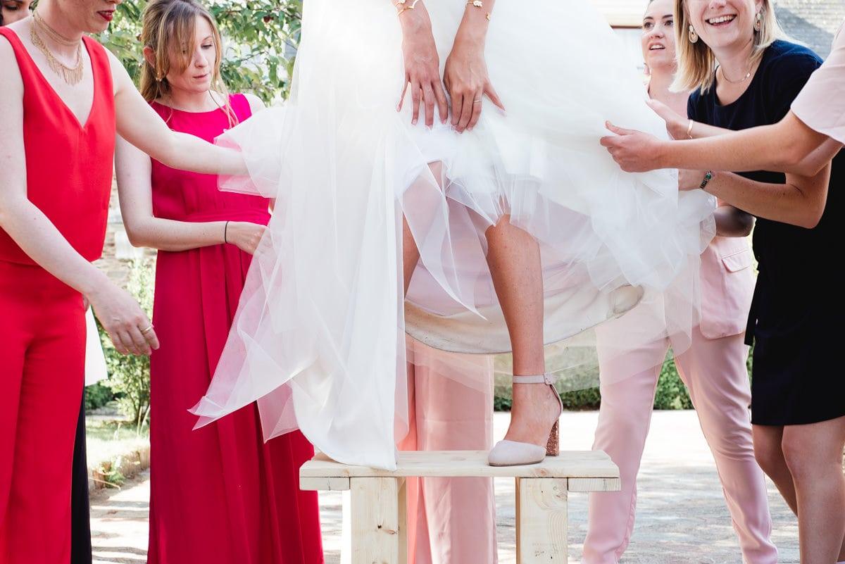 la mariée se tient en équilibre sur un banc avant la photo de groupe avec ses copines