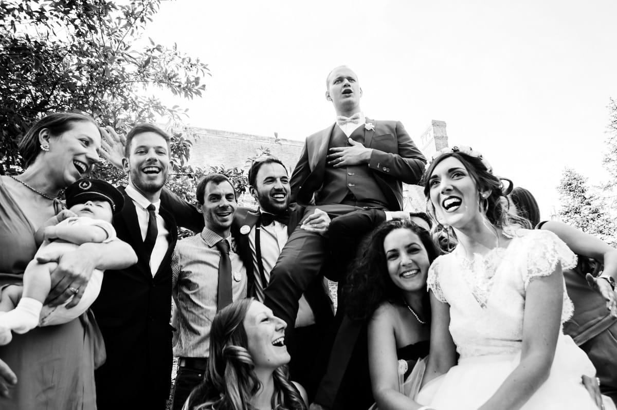 Le marié est porté par ses copains lors d'une photo de groupe naturelle au château de la colaissière