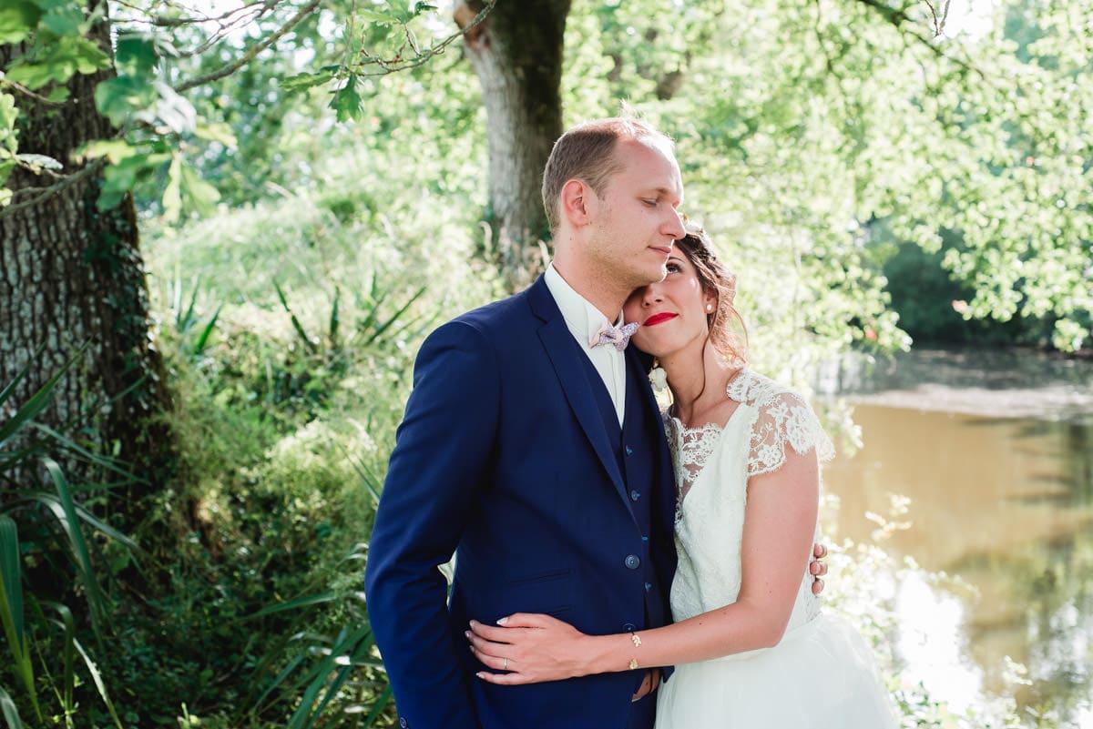 Un couple de jeunes mariés s'embrassent sous les chênes au chateau de la Colaissiere.