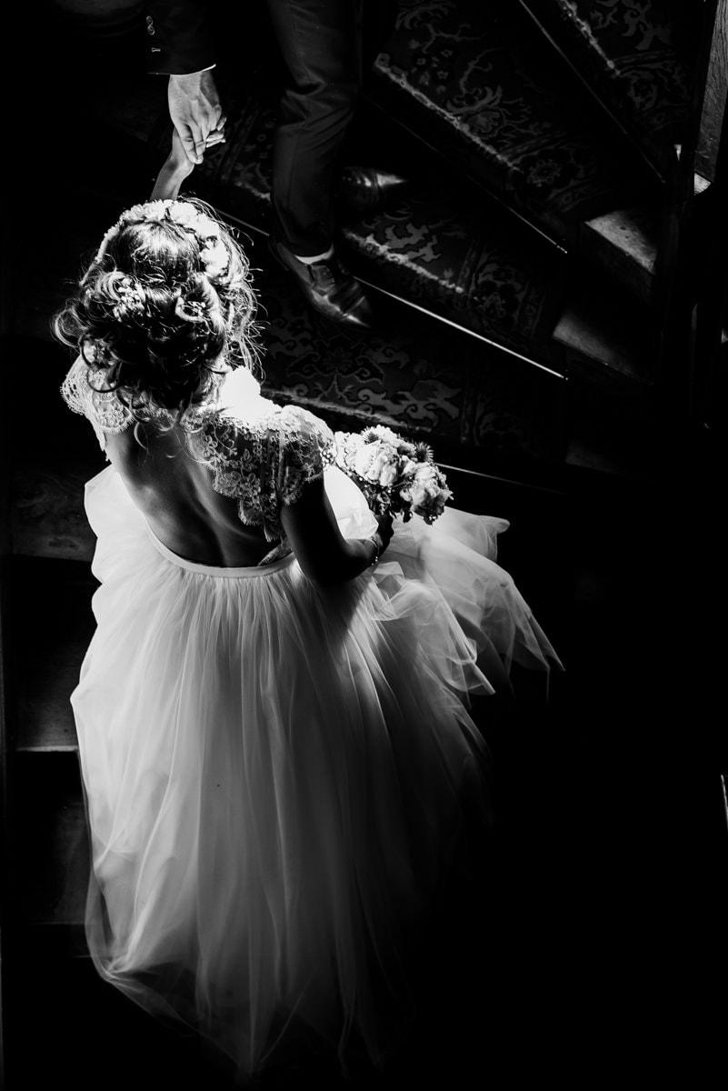La mariée en robe sur mesure de Kamélion, monte les escaliers du château de la colaissière