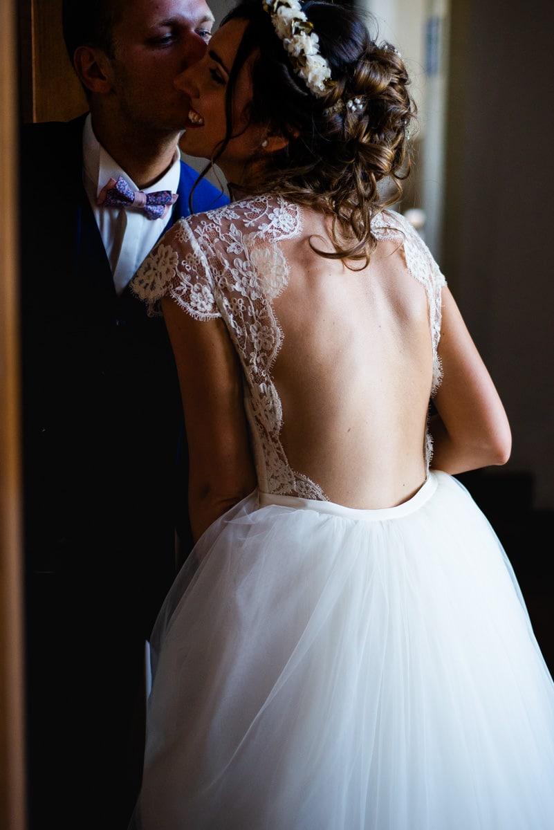 Le dos nu de la mariée prends la lumière dans les couloir du chateau, elle porte une couronne de fleur