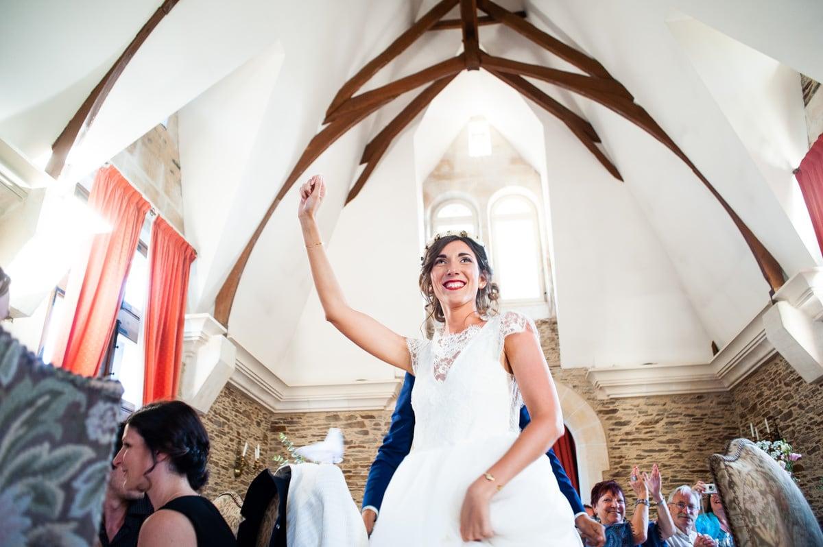 La mariée entre dans la salle de réception du château de la colaissière sous la charpente en bâteau retourné